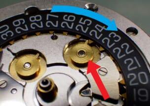 ジン 103 矢印で指した日送り車とカレンダー板が噛み合った状態です。青矢印はカレンダー板の回転方向です。